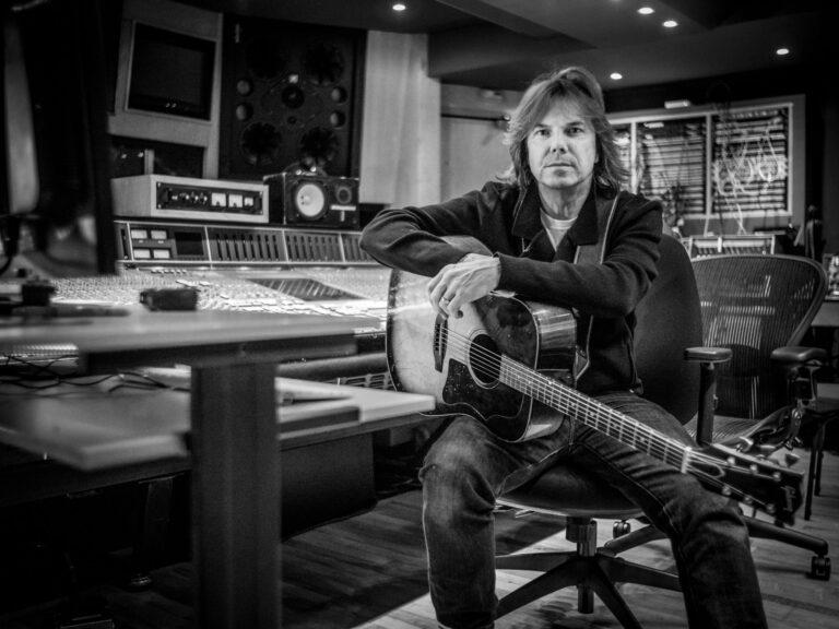 joey tempest assie avec une guitare